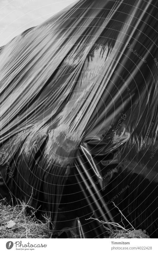 Einen Blick unter diese Plane werfen? Abdeckplane Kunststoff riesig geheimnisvoll Falten glänzend verbergen schützen Schutz Abdeckung Schwarzweißfoto