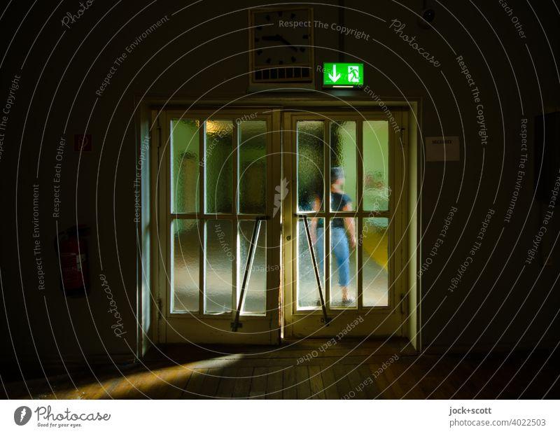 Warten vor der Doppeltür im Sonnenlicht Tür Frau hinten DDR Glastür retro Notausgang Zeichen Durchgang stehen durchsichtig Körperhaltung Stil Ostalgie Treptow