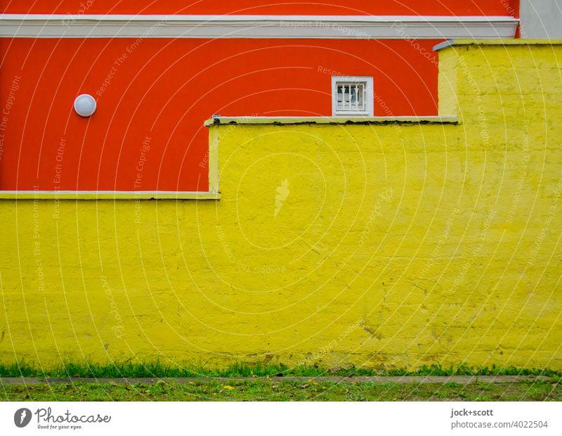 stufige Mauer trifft auf knallige Hauswand Fassade orange kleines Fenster Architektur Außenleuchte Stuck Putz gelb Wiese grün Anordnung Farbfläche Farbkontrast