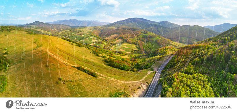 Landstraße in den Bergen. Abendliches Sonnenlicht auf Hügeln. Frühling grün ländlichen Landschaft. Straße Berge u. Gebirge Ansicht Panorama Antenne Serpentine