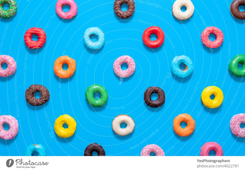 Mehrfarbige Donuts Draufsicht isoliert auf blauem Hintergrund. Glasierte Krapfen Muster. obere Ansicht ausgerichtet sortiert gebacken Bäckerei Schokolade