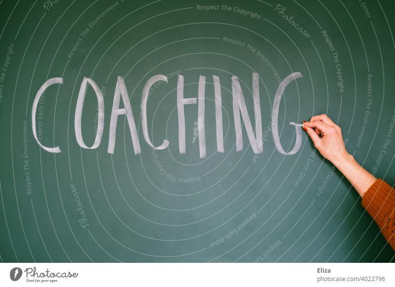 Hand schreibt das Wort Coaching auf eine Tafel Weiterbildung Karriere Fortbildung mindset Business Arbeit & Erwerbstätigkeit Zukunft coachen Bildung geschrieben