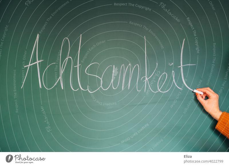 Hand schreibt das Wort Achtsamkeit auf eine Tafel schreiben Wohlbefinden Meditation Entspannung Buddhismus Bewusstsein Glück Stressabbau Achtsamkeitstraining