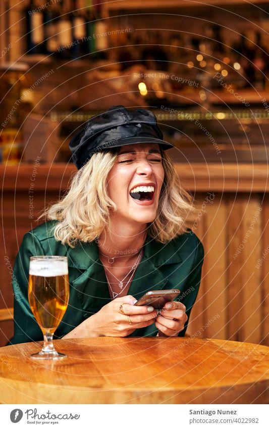 Frau schaut in einer Bar auf ihr Smartphone. Paar Erwachsener Glück Restaurant Lifestyle Kaukasier schön Fröhlichkeit trinken Lächeln Spaß Liebe Freude Feier