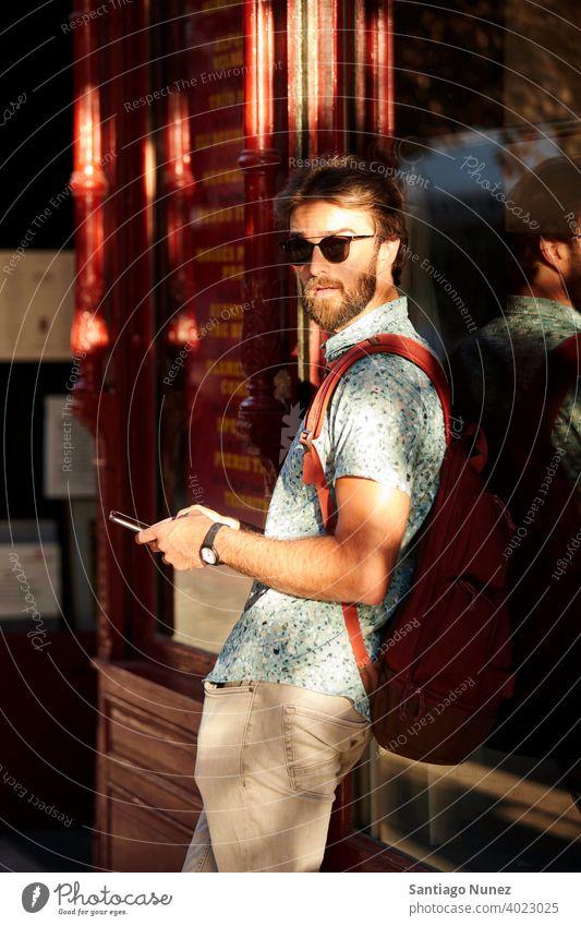 Mann schaut auf der Straße auf sein Telefon. Erwachsener Glück Lifestyle Kaukasier Fröhlichkeit Lächeln Spaß Liebe Freude Freizeit heiter Lachen Termin & Datum