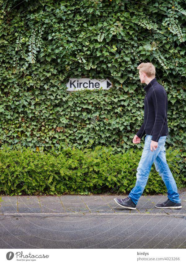 """Junger Mann wendet sich von der Kirche ab und geht in entgegengesetzte Richtung. Kirchenaustritt, richtungsweisendes Schild """"Kirche"""" umrahmt von Efeu Wut"""