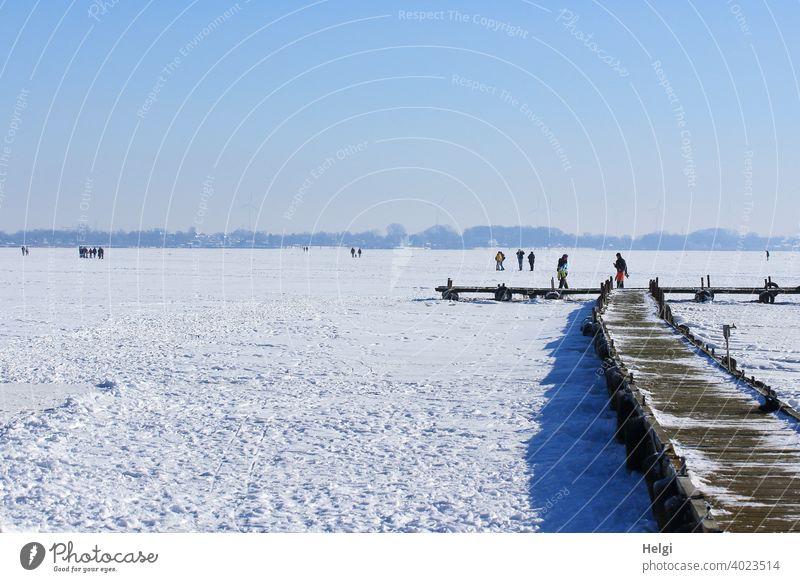 zugefrorener See mit Schnee, Holzsteg und Menschen, die auf dem Eis stehen und gehen Winter Kälte frieren Dümmer See Steg Weite Licht Schatten Sonnenlicht