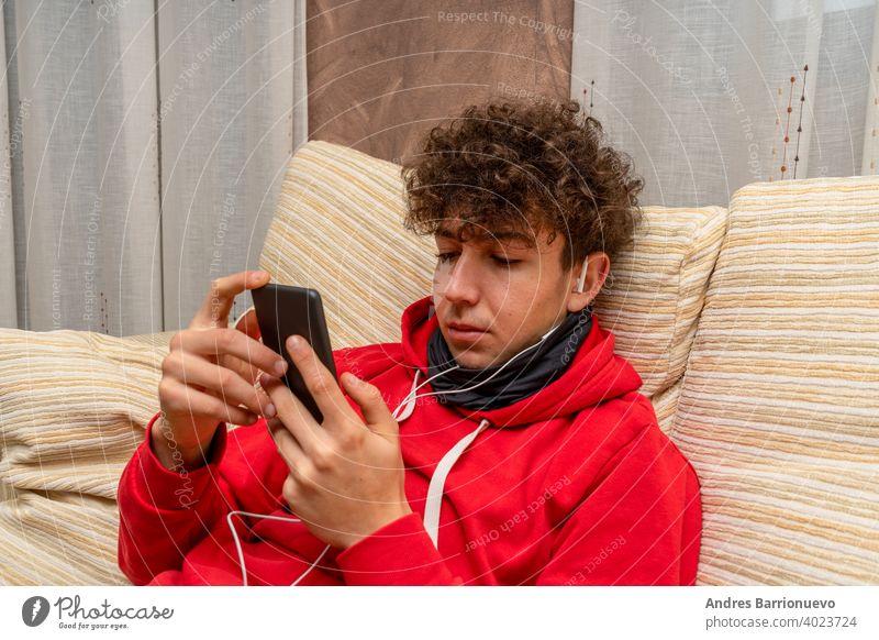 Junger attraktiver Mann mit lockigem Haar und rotem Sweatshirt, der im heimischen Wohnzimmer ein Handy benutzt und eine Maske trägt, um sich vor dem Coronavirus zu schützen