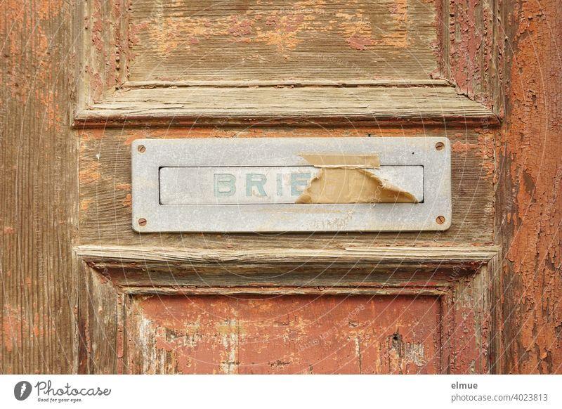 """alter, beklebter Briefkastenschlitz mit einer Klappe, auf der """"BRIEFE"""" steht, aus Metall in einer alten Holztür, an der die braune Farbe abblättert / Brief schreiben / E-Mail / Briefkastenfirma"""