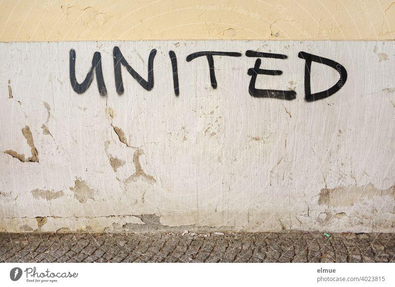 """""""UNITED"""" steht in schwarzen Großbuchstaben an der grauen, alten, verputzten Wand / verbunden / Schmiererei united vereint Fassade vereinigt Losung Graffito"""