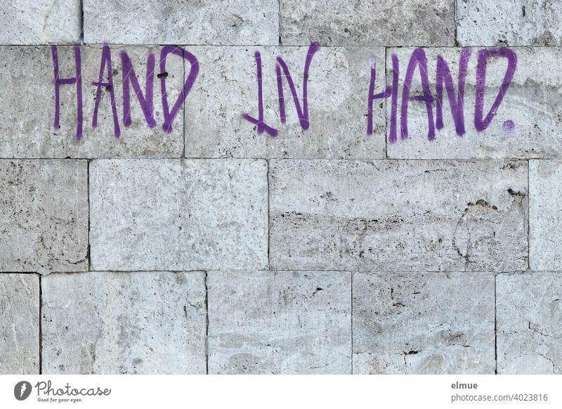 """""""HAND IN HAND"""" steht in lila Druckbuchstaben an der grauen Natursteinwand / gemeinsam Hand in Hand Wand Fassade Losung Graffito Graffiti Schmiererei"""