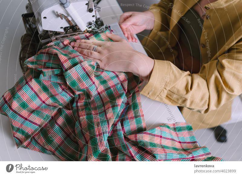 Draufsicht auf eine Frau bei der Arbeit an einer Overlock-Nähmaschine in ihrer Werkstatt, Bekleidung Material Gewebe Nähen kreativ Faser Sitzen Werkzeug
