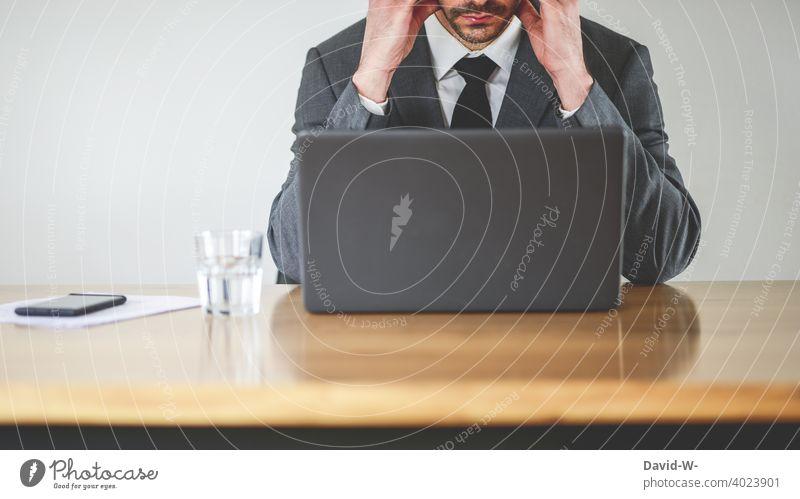 Mann im Anzug am Laptop Arbeitsplatz laptop Notebook überlastet angestrengt Kopfschmerzen konzentriert Schreibtisch Business businessmann Homeoffice