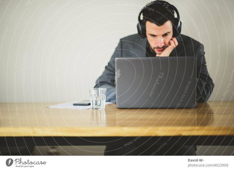 Mann arbeitet am Laptop / Notebook Tisch arbeiten sitzen konzentriert Headset surfen online business Arbeitsplatz zu Hause Homeoffice Prüfung