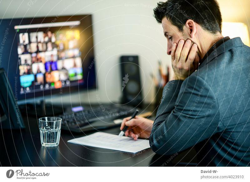 Mann sitzt am Computer und checkt Daten auf einem Zettel arbeiten Stift checken kontrollieren prüfen Liste durchgehen überprüfen Business Anzug Homeoffice