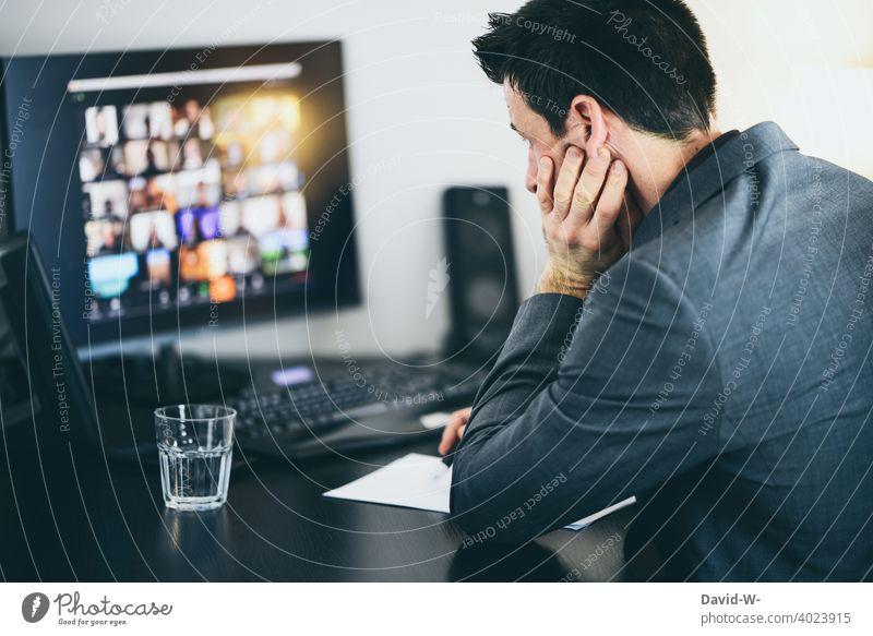 Mann arbeitet am Computer arbeiten Konferenz online Homeoffice Besprechung genervt erschöpft gelangweilt Schreibtisch