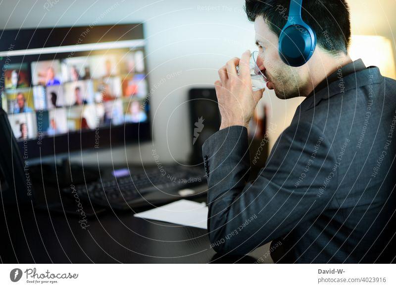 bei der Arbeit im Homeoffice arbeiten Mann Meeting Computer Konferenz Konferenzschaltung vernetzt zu Hause Internet Arbeitsplatz Schreibtisch konzentriert