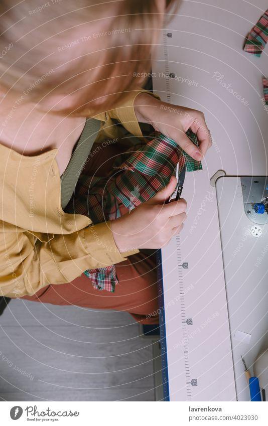 Draufsicht auf eine Frau bei der Arbeit in ihrer Nähwerkstatt, Nähen Gewebe Schneider Material Näherin Bekleidung Nadel Handwerk Faser Textil Business Arbeiter