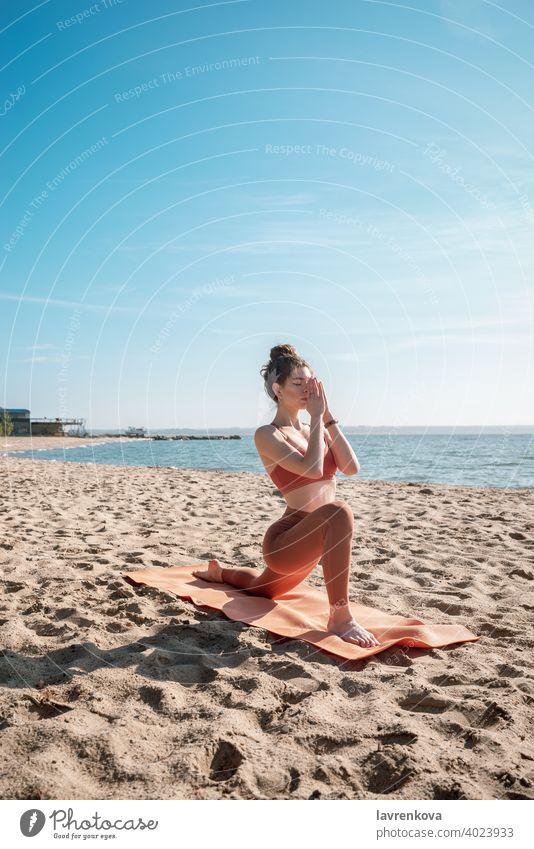 Junge Frau in orangefarbenem Oberteil und Leggins beim Üben der Sichel-Lunge-Pose (Anjaneyasana) am Strand am Morgen Übung Yoga jung praktizieren im Freien