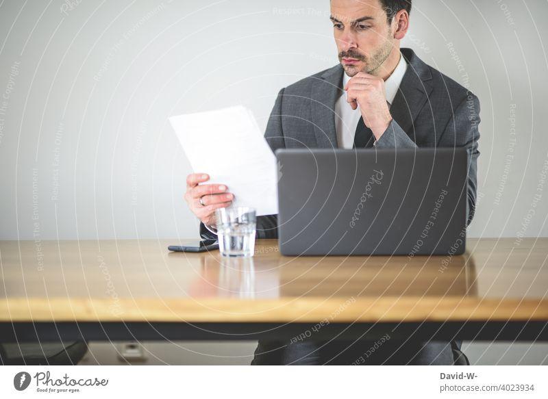 skeptischer Mann am Laptop bei der Arbeit arbeiten überprüfen homeoffice kontrollieren Arbeitsplatz Notebook Homeoffice Skeptiker zweifeln unsicher kritisch