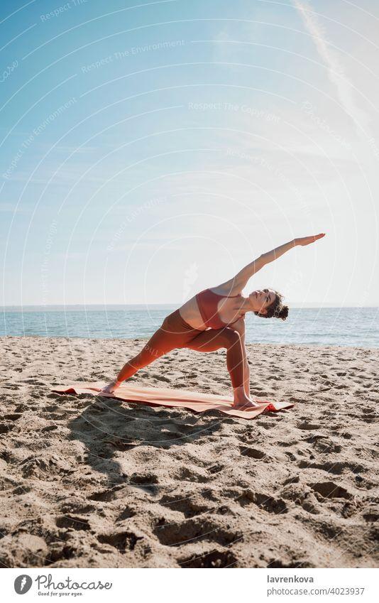 Junge Frau in orangefarbenem Oberteil und Leggins beim Üben der Erweiterten Seitenwinkelstellung (Utthita Parsvakonasana) Übung Pose Yoga Strand jung