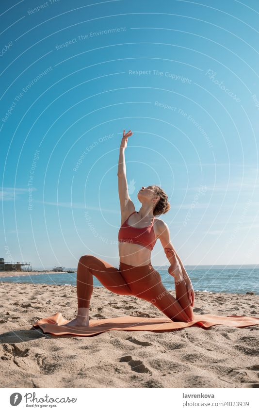 Junge Frau in orangefarbenem Oberteil und Leggins beim Üben der Mondsichel-Pose (Anjaneyasana-Variante) an einem Strand am Morgen Übung Yoga jung praktizieren