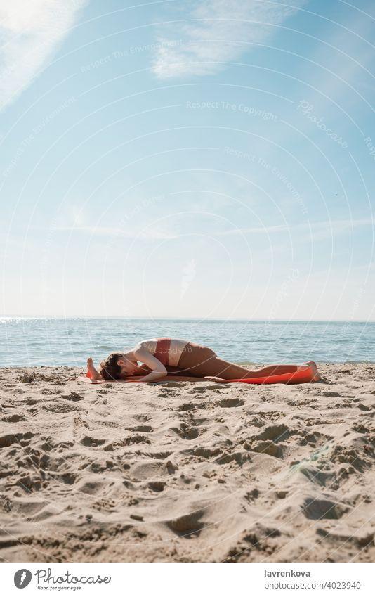 Junge Frau in orangefarbenem Oberteil und Leggins beim Üben der Yoga-Spalt-Variante (Hanumanasana) an einem Strand am Morgen passen Training Spagat hanumanasana
