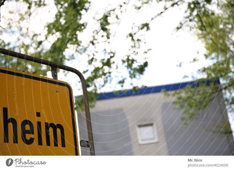 WohnHeim Haus Schilder & Markierungen Wohnsiedlung Seniorenheim Altersheim Schriftzeichen Typographie Wort Stadtteil Wohnheim Fenster Fassade Hinweisschild Baum