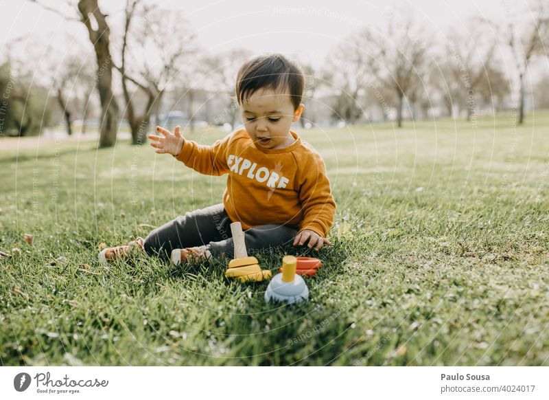 Kleinkind spielt mit woodem Spielzeug im Park Frühling im Freien Spielen Kindergarten Außenaufnahme Kindheit Freude Farbfoto Spielplatz Mensch Tag Glück