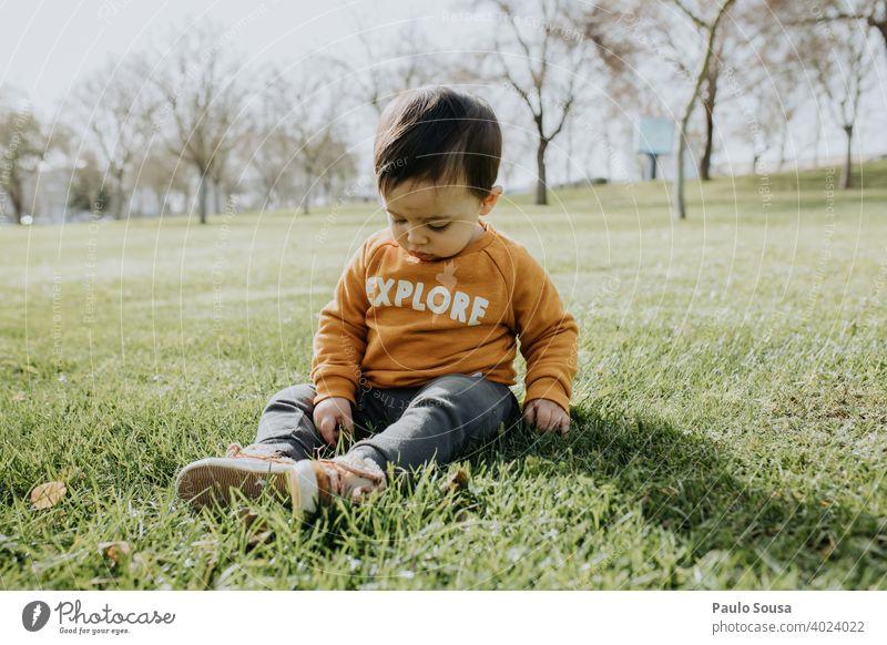 Kind spielt im Park sitzen Sitzen Gras Kindheit 1-3 Jahre Kaukasier Farbfoto Außenaufnahme Tag Lifestyle Mensch Fröhlichkeit Kleinkind Glück authentisch Freude