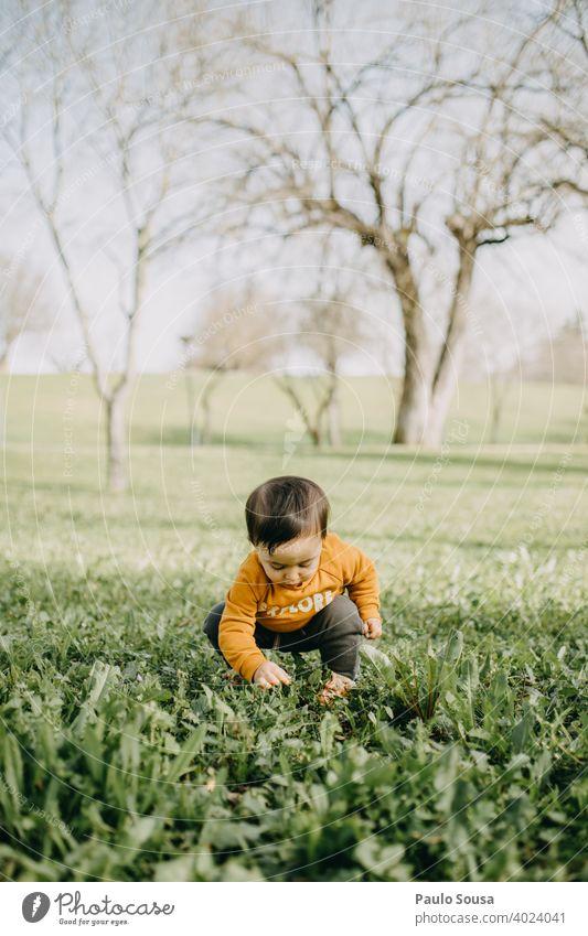 Kind spielt im Park Kaukasier 1-3 Jahre Farbfoto Kindheit Mensch Kleinkind Tag Außenaufnahme Lifestyle Freude niedlich Gras Frühling Leben authentisch