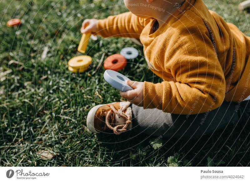 Kind spielt mit Spielzeug im Gras Kindheit unkenntlich Aktivität Freude Glück im Freien wenig Lifestyle Natur Spielen Bildung Kaukasier spielerisch Fröhlichkeit