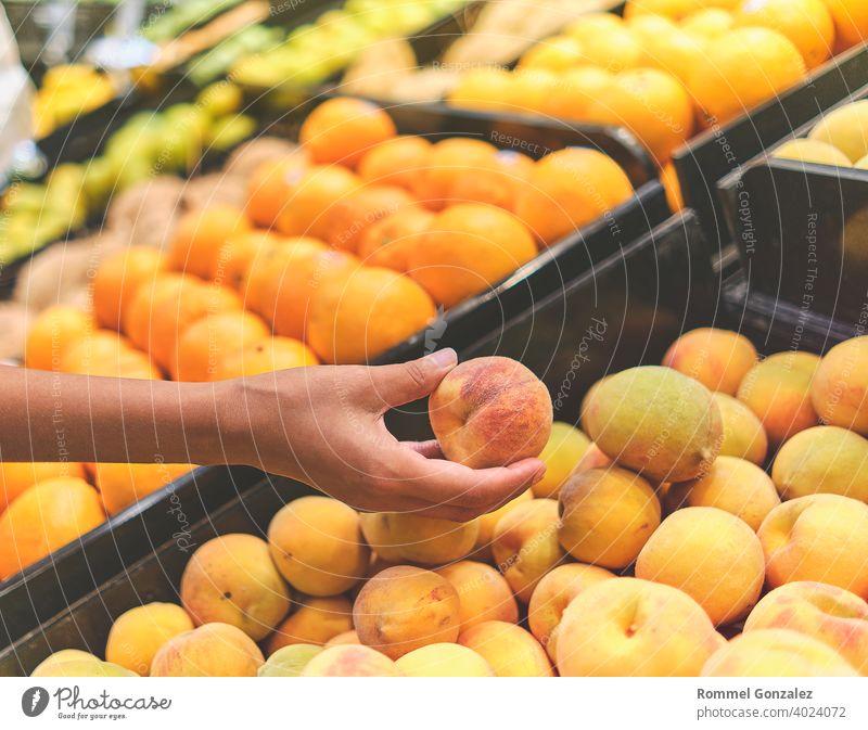 Junges Mädchen wählt Pfirsich in einem Lebensmittelgeschäft. Konzept der gesunden Ernährung, Bio, vegetarisch, Diät. Selektiver Fokus. Früchte Großhandel