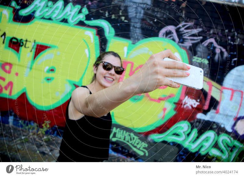 Junge Frau macht ein Selfie vor einer Graffiti Wand Smartphone Eitelkeit jung Selbstportrait Gesicht Telefon Handy Mobiltelefon kamera posen Pose posieren