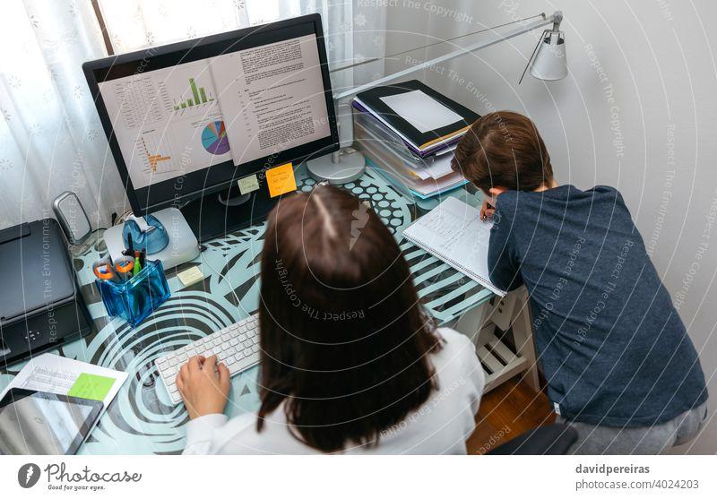 Frau arbeitet von zu Hause aus, während ihr Sohn studiert Telearbeit Arbeit Familie Schlichtung Junge studierend Coronavirus Sperrung covid-19 arbeiten Kind