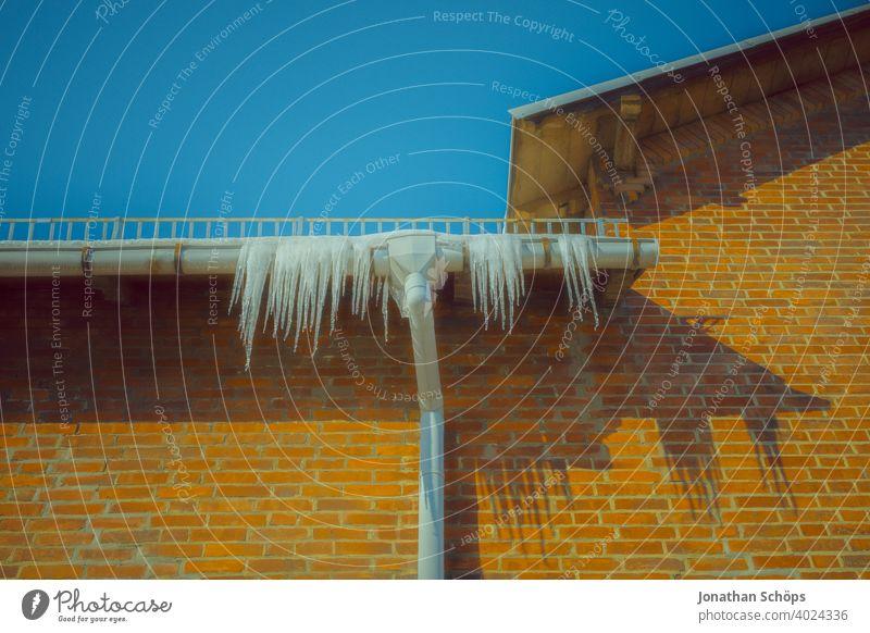 Eiszapfen an der Dachrinne an Backstein Haus Fassade Architektur Backsteinhaus Backsteinhaussiedlung Dachkante Fallrohr Froschperspektive Gebäude Gefahr