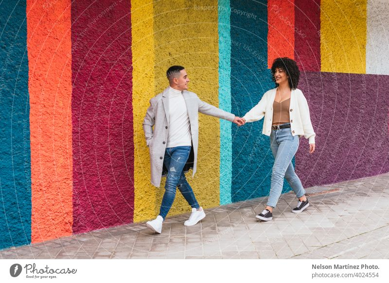 Junges glückliches Paar, das sich an den Händen hält und durch einen Bürgersteig gegen eine bunte Wand läuft Straßenbelag farbenfroh streifen jung Beteiligung