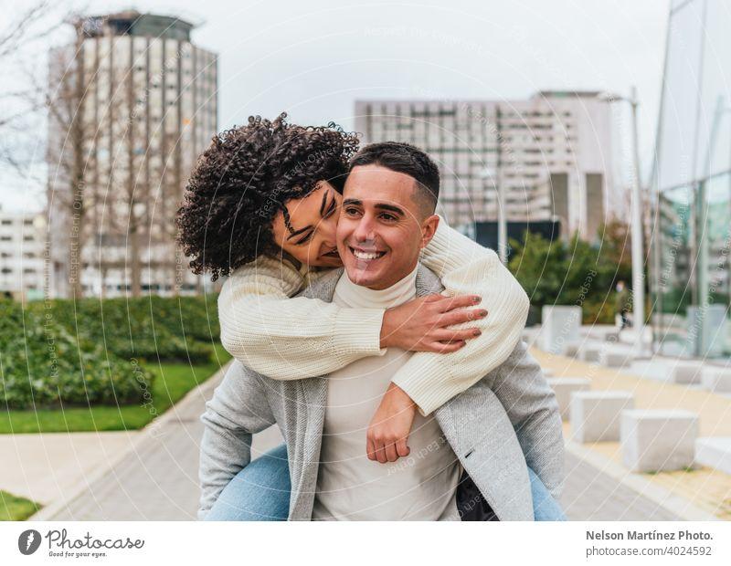 Shallow Fokus eines jungen lächelnden Mannes trägt seine Freundin auf dem Rücken tragen heiter Paar seicht Jugend Lächeln im Freien Erwachsener Glück Frau