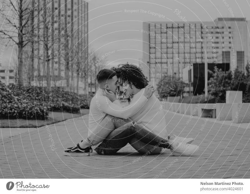 Schwarz und weiß flachen Fokus von einem romantischen jungen Paar küssen auf einem Bürgersteig unter einem bewölkten Himmel Küssen im Freien Straßenbelag seicht