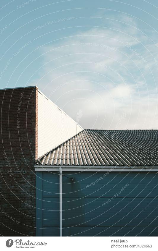 Geometrische Formen, wo ein Wellblechdach auf eine sonnenbeschienene Lagerhalle trifft. Architektur Industrie Wirtschaft Minimalismus minimalistisch