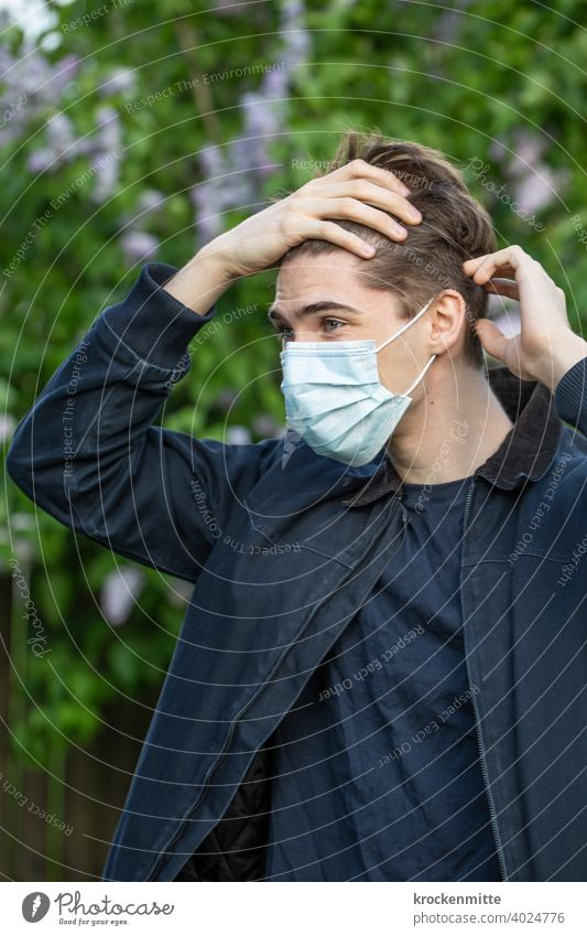 Jugendlicher mit Schutzmaske greift sich an die Stirn Teenager im Freien Sommer jung coronavirus covid-19 COVID Coronavirus Corona-Virus Gesundheit