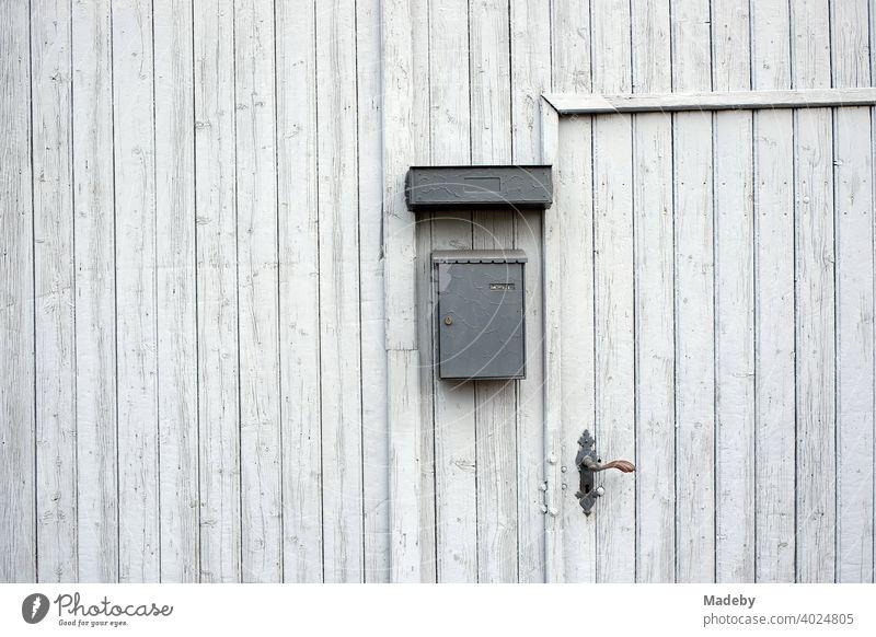 Eingangstür in einem alten hellgrauen Scheunentor aus Holz eines Bauernhof in Wettenberg Krofdorf-Gleiberg bei Gießen in Hessen Holztor Tor Scheunentur Haustür