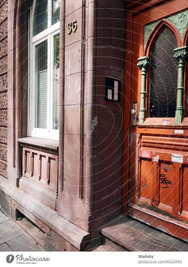 Altbau aus rotem Sandstein mit schöner Holztür im Jugendstil bei Sonnenschein im Nordend von Frankfurt am Main in Hessen Tür Haustür Wohnungstür Eingang