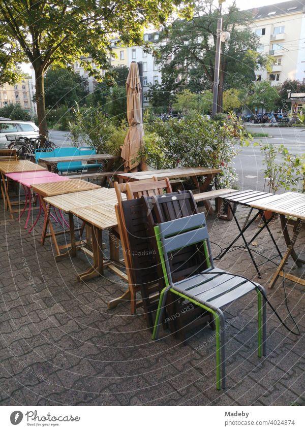 Bistrotische und Stühle auf dem Bürgersteig mit Verbundpflaster vor einem geschlossenen Bistro im Nordend von Frankfurt am Main in Hessen Tisch Stuhl