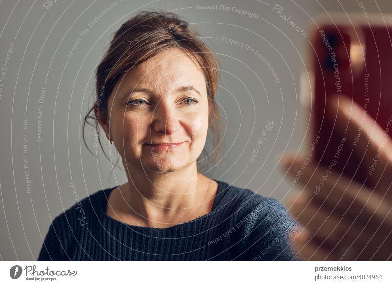 Frau macht Videoanruf mit dem Mobiltelefon. Im Gespräch mit Verwandten. Spaß beim Selfie-Foto machen mit dem Smartphone. Verbindung mit der Familie aus der Ferne