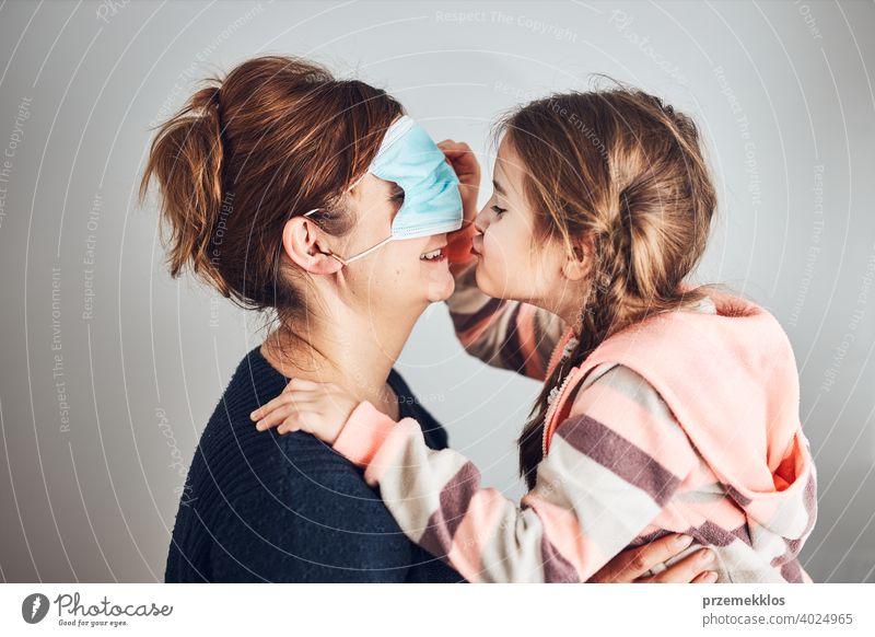Kleines Mädchen bewegt die Gesichtsmaske ihrer Mutter auf die Augen und gibt ihrer Mutter einen Kuss. Lustige Momente während der Covid-19-Pandemie Zuneigung