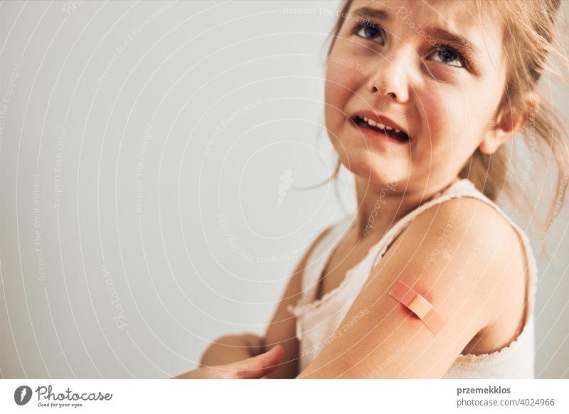 Kleines Mädchen, das nach der Impfung Schmerzen hat, hat einige Nebenwirkungen. Rötung, Schwellung, Gliederschmerzen und Kopfschmerzen als Reaktion nach der Impfung