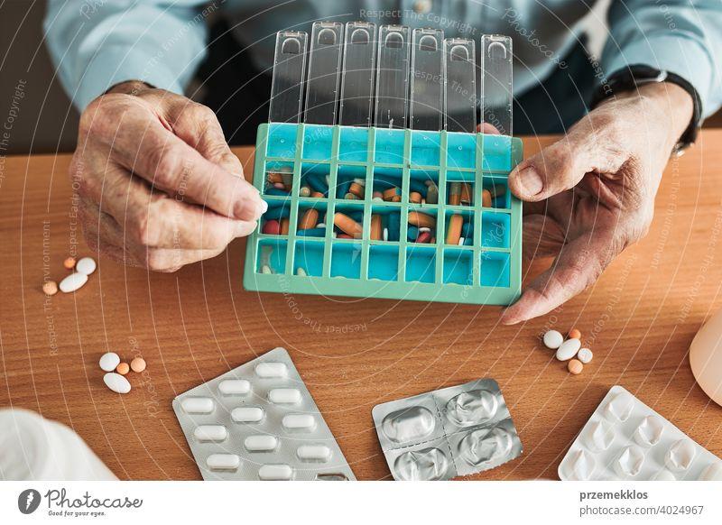 Senior Mann organisiert seine Medikamente in Pillenspender. Senior Mann nimmt Pillen aus Box Tablette Krankheit Spender geduldig Verschreibung medizinisch