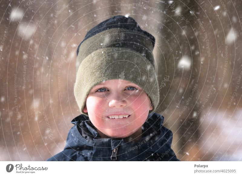 Junge im Schnee mit einer Strickmütze natürlich Wolle Kleidung hübsch gestrickt Umwelt Nahaufnahme Schneeflocke Lächeln Lifestyle Wetter frieren im Freien Frost