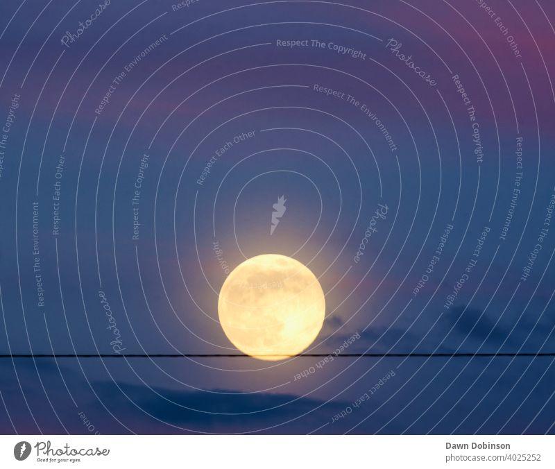 Vollmond, der auf einem Draht im Dämmerungshimmel zu balancieren scheint Gleichgewicht Außenaufnahme Himmel Abend blau Farbfoto Natur Wolkenfetzen rund